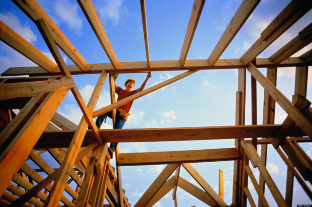 Carpenter measuring frame of unfinished house, low angle view