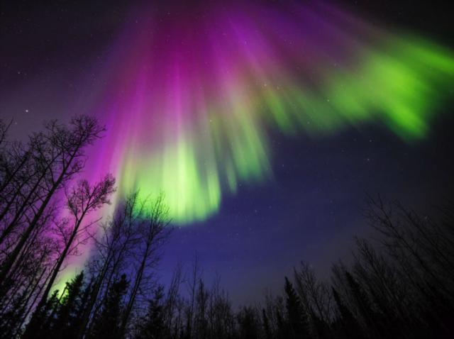 7. irudia: irudia: Eguzkitik datozen partikulen eta ekaitz geomagnetikoen ondorioz sortzen dira aurorak poloetatik gertu. Koloreak partikulen arteko talketan askatzen den energiari buruzko informazioa ematen du. (Argazkia: NASA eta Sebastian Saarloos)